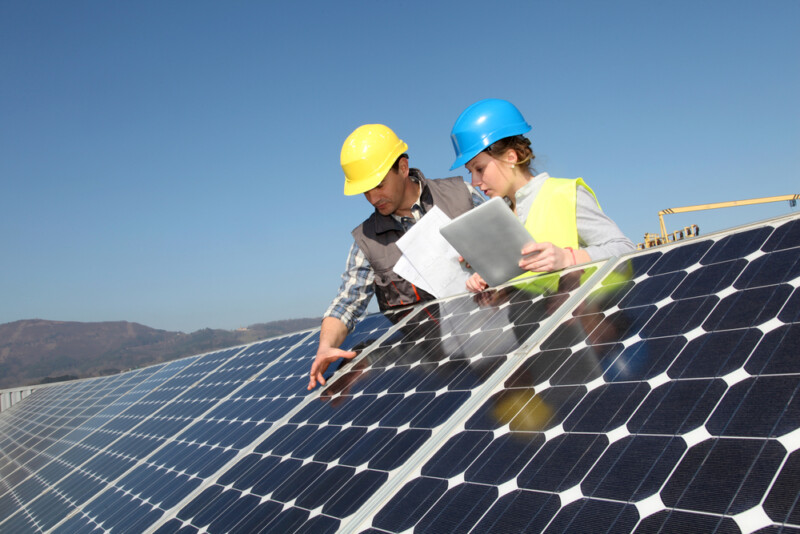 Two workers examine a solar panel